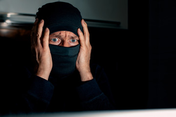 Masked hacker holds his head by two hands and looking at the monitor. Epic fail.