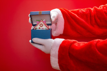 Santa Claus opening a present box with  Christmas house model on red background