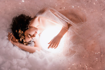 gentle image of angel sleeping next to the moon in pink light clouds, naked body of slim girl lying in a mist, covered with glitter sequin, princess of the night with dark hair and a wonderful wreath