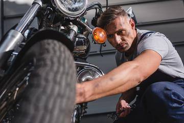 handsome adult mechanic fixing motorcycle tire in garage
