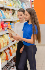 Teen girls shopping in supermarket reading product information.Choosing daily product