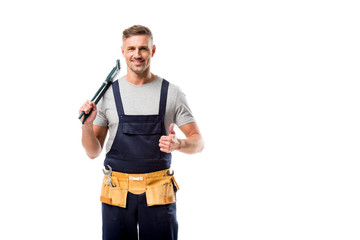 smiling plumber holding pipe wrench and showing thumb up sign isolated on white Wall mural