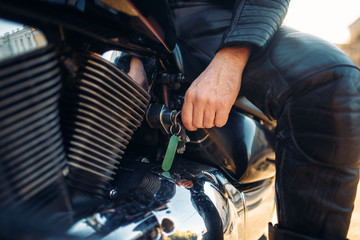 Biker inserts the key in the ignition of chopper
