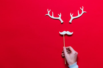 Festive reindeer face made from white antlers and a white moustache on a red background