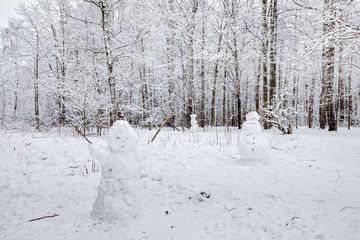 Three snowmen in forest