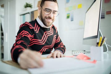 Cheerful enterprising handsome bearded manager in glasses sitting at table with computer and writing out ideas while working in modern office