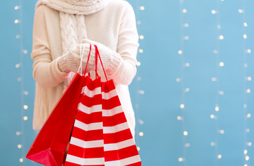 Woman holding shopping bags on a shiny light blue background