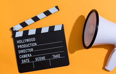 Movie slateboard clapper with megaphone on a orange background