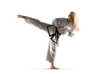 Woman in kimono practicing taekwondo. Isolated