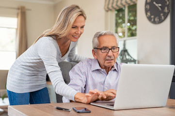 Daughter helping old father with laptop