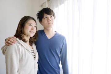 窓辺で寄り添う若いカップル