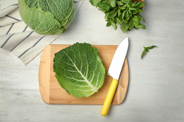 Flat lay composition with savoy cabbage and basil on white wooden background