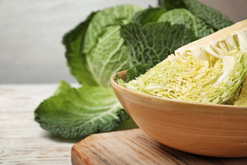 Bowl with cut savoy cabbage on table, closeup. Space for text