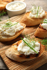 Toasted bread with tasty cream cheese on wooden board