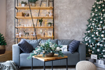 Interior of modern living room with comfortable sofa decorated with Christmas tree and gifts