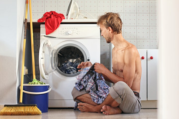 Male housewife or bachelor concept. Handsome young man loads the laundry into the washing machine