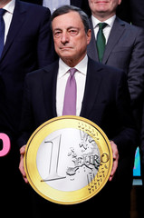 ECB President Draghi takes part in a group photo while celebrating the 20th anniversary of the euro during a eurozone finance ministers meeting in Brussels