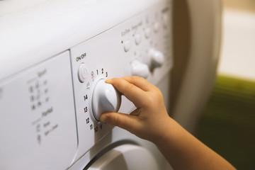 Child hand on the washing machine button