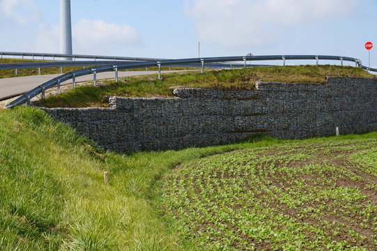 Strengthening the steep slope. A fragment of the retaining wall of the road made of gabions.