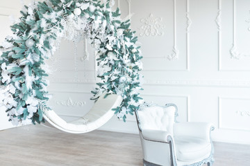 Christmas minimalism. White sitting ring with christmas decoration in modern white classical interior. Minimal christmas new year concept.