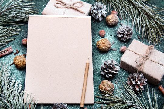 Tło na Boże Narodzenie  z pustą kartka papieru otoczoną świątecznymi dekoracjami. Miejsce na tekst. List do Mikołaja lub Świąteczna lista zakupów