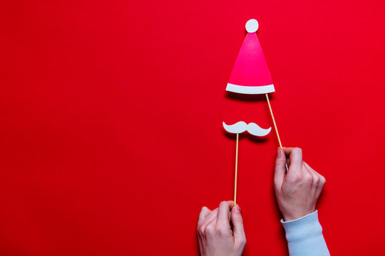 Hands holding Santa Claus Christmas photobooth props on a red background