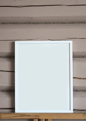 White paper blank interior poster, isolated vertical mock up with frame on beige wooden wall background.