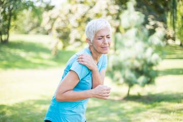 Senior sporty woman having shoulder pain