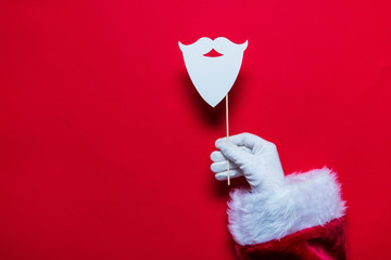 Santa Claus Christmas hand holding a beard against a red background