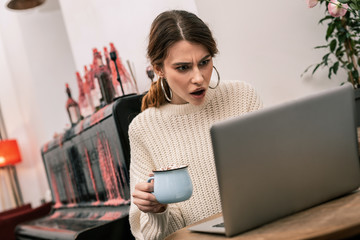 Outraged woman working in a cafe with her computer