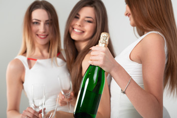 Three young woman in elegant dresses having fun, smiling, dancing and drinking champagne in studio on white background. Christmas party celebration concept.
