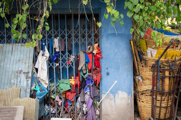 Garbage and rags or tatter with green leaves or ivy such as bamboo and plastic buckets, were hung and lined up on closed steel doors.