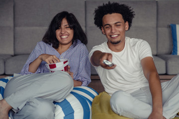 Image of smiling couple sitting on floor near sofa at home and looking aside while eating popcorn