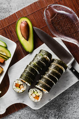 vegan ready-made sushi on the table in fish plates. rolls with fried tofu, cucumber, boiled carrots and fresh avocado. healthy vegan food