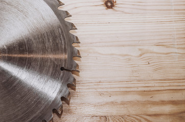 Circular saw on a wood background. Workshop. Manufacture of wooden products. Joiner's cutting tool