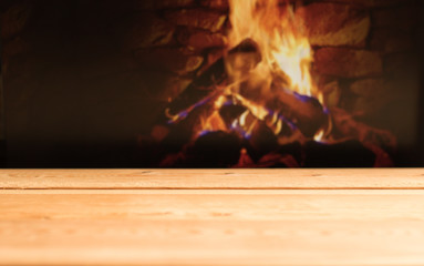 Wooden table on a blurred background of burning fire in fireplace with copy space for your message.