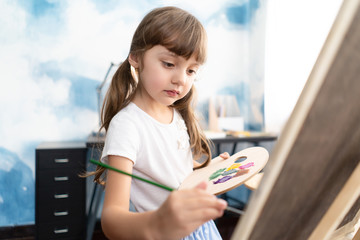 Portrait of a beautiful liitle girl draw and paint in canvas at her home.Concept of early childhood education, happy family, parenting