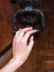 Hand and old rusted knocker on brown wooden door. Part of body, Vintage style and Decorated concept