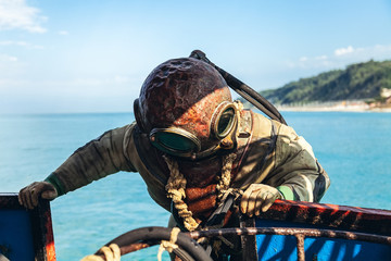 a diver in old equipment plunges into the sea