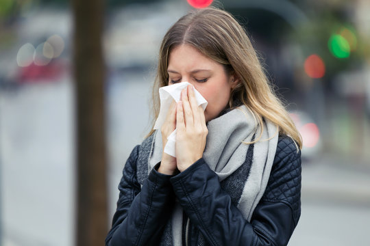 Illness young woman sneezing in a tissue in the street.