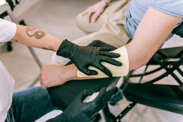Tattoo master putting her hand on sticker of future tattoo