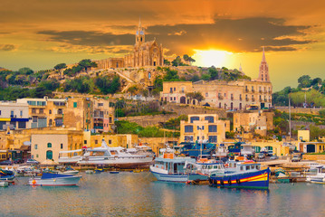 Beautiful cityscape over Gozo island, medieval architecture of castle and boats on the harbor of Malta