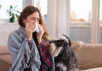 Girl covered with blanket blowing nose at home