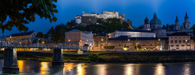 Panoramic Picture of Salzburg and Salzach River at Night, the Historic Centre of the City of Salzburg is a UNESCO World Heritage Site. Hohensalzburg Castle is one of the most preserved baroque castles