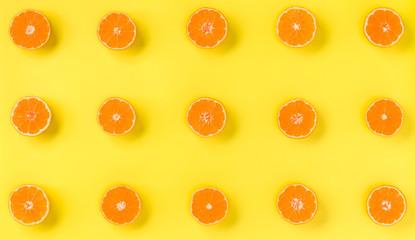 Fruit pattern of fresh mandarin slices on yellow background. Flat lay, top view. Pop art design, creative summer concept. Half of citrus in minimal style. Tangerine.