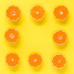 Fruit pattern of fresh mandarin slices on yellow background. Flat lay, top view. Pop art design, creative summer concept. Half of citrus in minimal style. Tangerine.