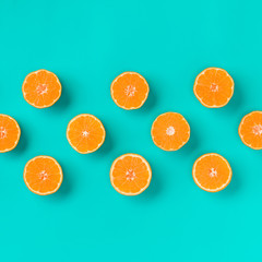 Fruit pattern of fresh mandarin slices on blue background. Flat lay, top view. Pop art design, creative summer concept. Half of citrus in minimal style. Tangerine.
