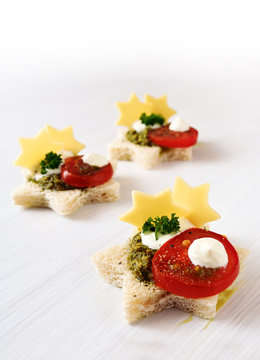 creative christmas canapes in star shape with tomato, pesto and cheese, light background fades to white, copy space