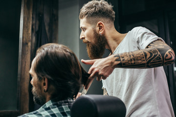 Thoughtful barber looking at the mirror while touching hair of client