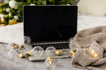 Image of open laptop with white screen on wooden table in front of christmas tree background. For mockup